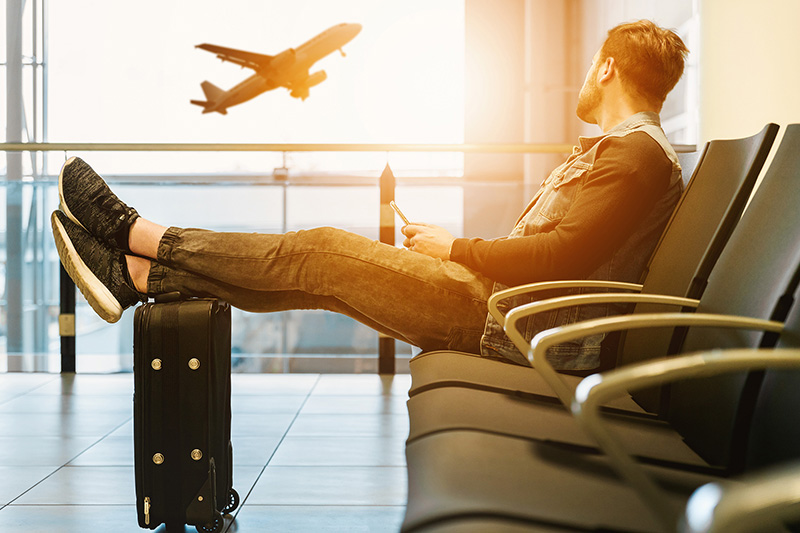 Man waiting the flight with a mobile phone