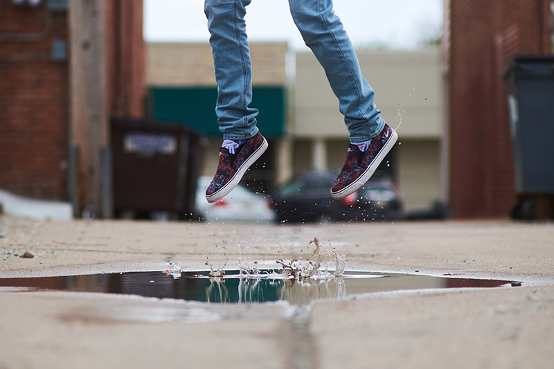 Person jumping in a puddle