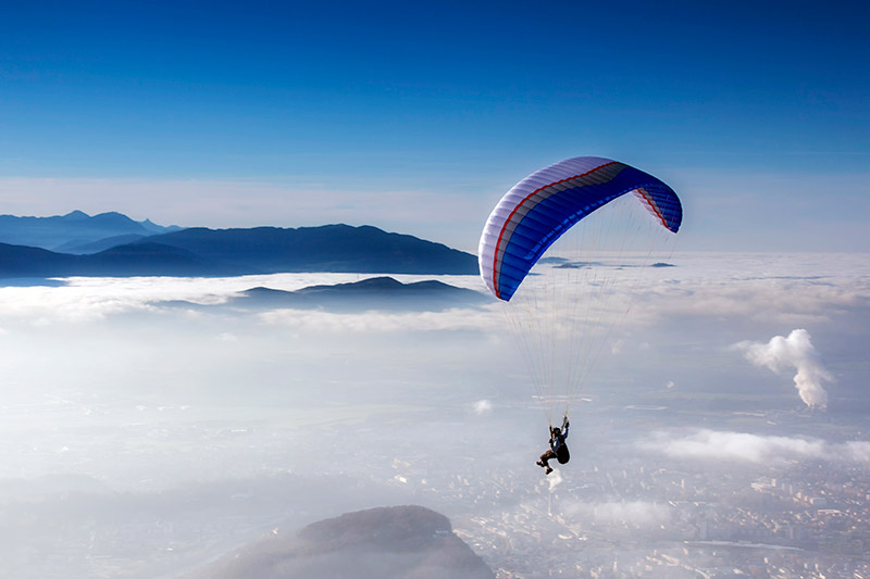 Person parachuting above the clouds