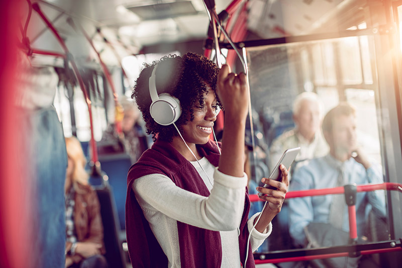 Woman standing on a bus with headphones on using her mobile phone